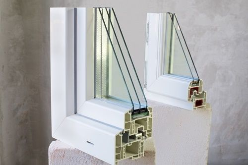 Two sample of PVC windows stands on a concrete block on a concrete wall background